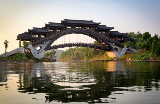 由红木建造的彩虹桥,世界上唯一一座红木桥   12月22日,记者走进红木小镇,了解自筹备建设一年半时间之后红木小镇的面貌,建设期中出现的问题以及小镇建设的前景展望。据中国年年红家具集团的董事长助理杨振介绍,红木小镇建设已形成较为完备的规划理念,目前建设进行的十分顺利,吸引不少投资者竞相投资。小镇囊括以巧夺天工的红木工艺以及融入佛道文化的红木小镇为特色的旅游业,以水上演出、名俗文化为特色的文化产业,以亚洲最大的红木家具制造为特色的制造业,以前店后厂模式形成的中国工匠一条街为特色的商业,以及新型住宅区和引