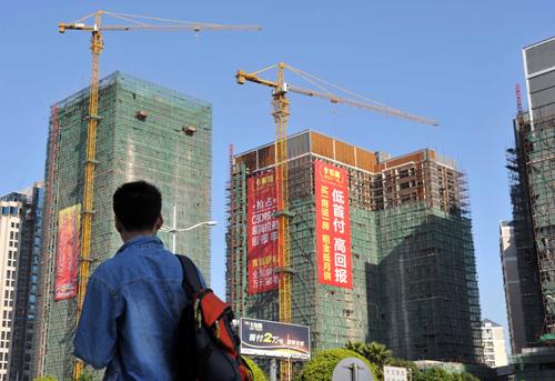 一位市民观看东莞市的一个在建楼盘。新华社发