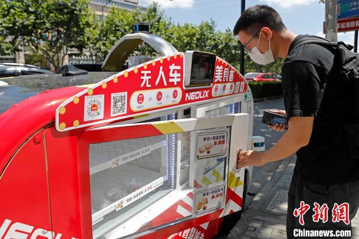 市民在无人餐车边扫码购买早餐。 殷立勤 摄